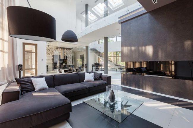 Просторная современная гостиная с угловым диваном и стеклянным журнальным столиком