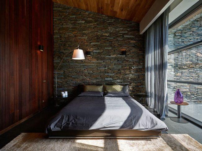 Необычная спальня с деревянной стеной и стеной из декоративного камня у изголовья кровати