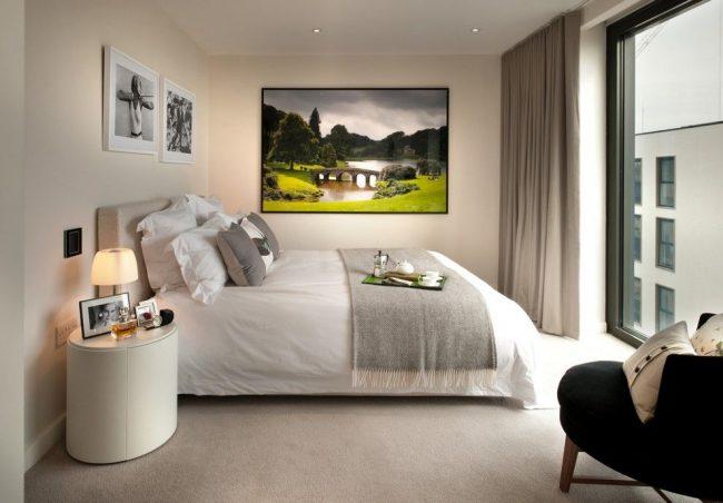 Небольшая уютная спальня с маленьким светильником на прикроватной тумбе