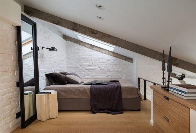 Светлая мансардная спальня с прикроватным светильником, закрепленным на стене над кроватью