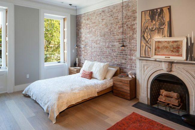 Современная спальня с кирпичной стеной у изголовья и потолочными светильниками