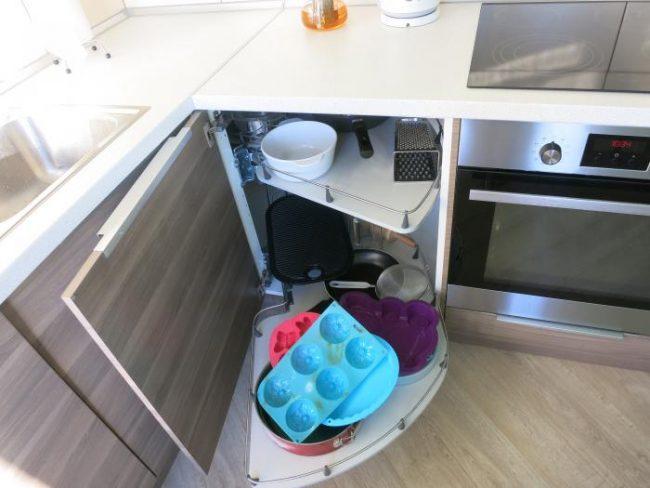 Удобные угловые полки для хранения посуды в тумбе под мойкой