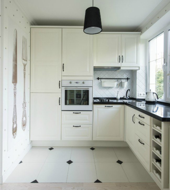 Уютная угловая кухня молочного цвета с мойкой в углу у окна и большой тумбой под ней