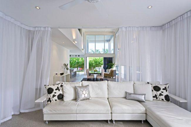 Круговые шторы из белой тюли отделяют зону отдыха и создают уют