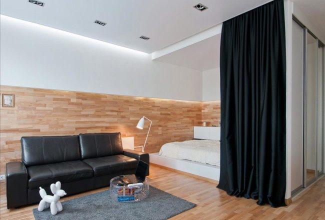 Красивые черные шторы из плотной ткани отделяют спальное место от зоны гостиной