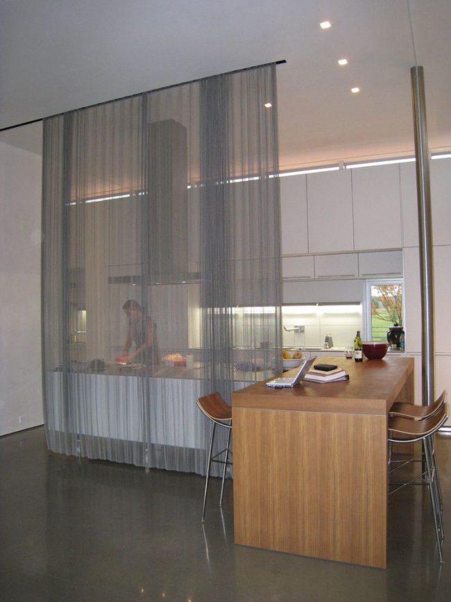 Полупрозрачная серая штора скрывает рабочую зону кухни