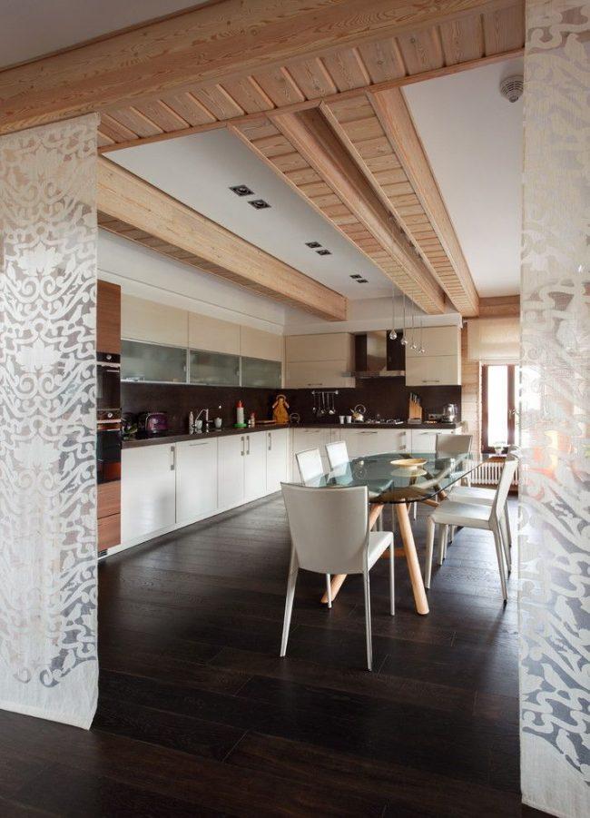 Полупрозрачные шторы с белым узором служат вместо дверей между кухней и комнатой