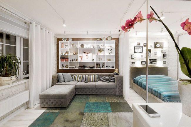 Современный интерьер гостиной с зонированием пространства с помощью легких белых штор