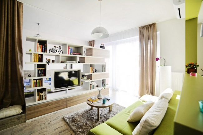 Зонировать пространство помогает декоративная мебельная стенка и штора