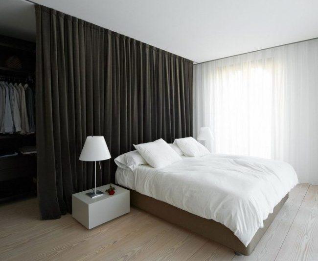 Гардеробная в спальне аккуратно скрыта за плотной шторой