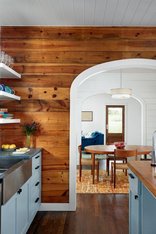 Арка с гладкой поверхностью и отделка стен деревом на кухне загородного дома