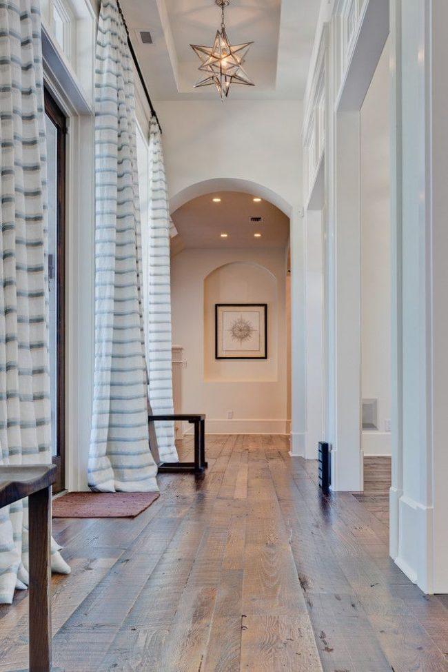 Широкий коридор в светлых тонах в жилище с высокими потолками
