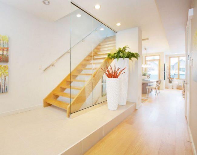 Нестандартное решение: комбинирование ваз разной высоты и с разными растениями в холле дома