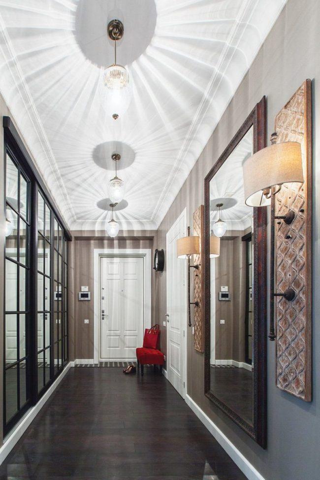 Красивый холл с зеркальной стеной и большим зеркалом напротив в деревянной раме