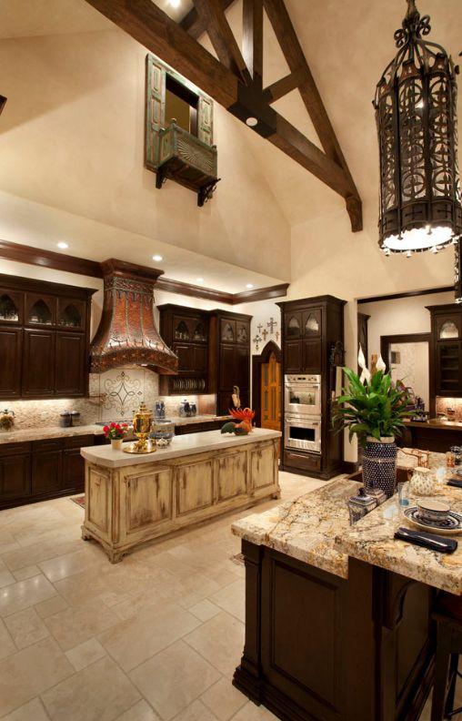 Кухня в готическом стиле: темный гарнитур с мраморной столешницей, точечное освещение зоны готовки и кованный светильник над обеденный зоной