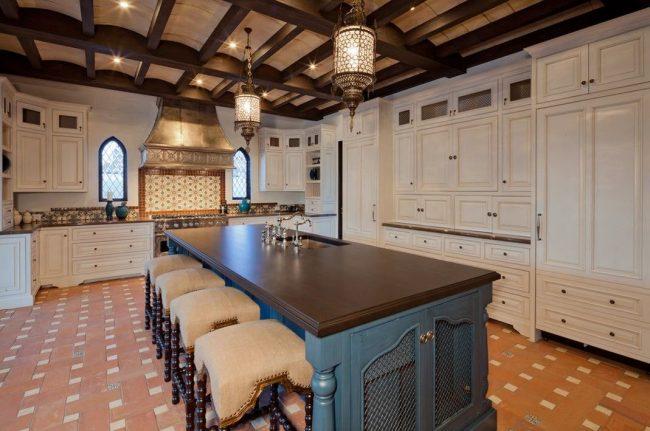 Кухня в марокканском стиле: белый кухонный гарнитур, контрастирует с зоной приготовления пищи