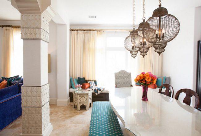 Обеденная зона в марокканском стиле: разделена от гостиной с помощью арочного проема. В качестве декора использованы традиционные подвесные светильники и ваза с цветами