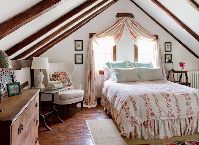 Установить кровать изголовьем к окну можно в мансарде: потолок в виде скатов крыши добавляет особого уюта комнате