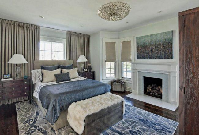 Источником тепла в комнате может стать и камин, который лучше расположить со стороны подножья кровати