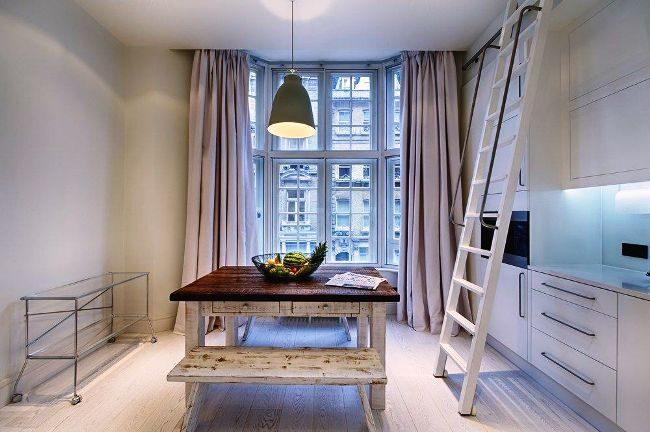 Тяжелые шторы в пастельных тонах украсят светлую кухню с панорамными окнами