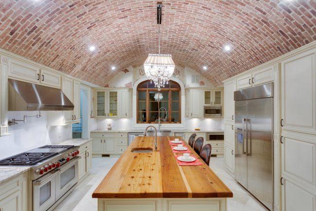 Роскошная светлая кухня с полукруглым потолком в кирпичной кладке