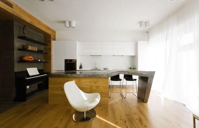 Украшением такой кухни-столовой выступает остров с массивной столешницей из натурального камня, переходящей в обеденный стол