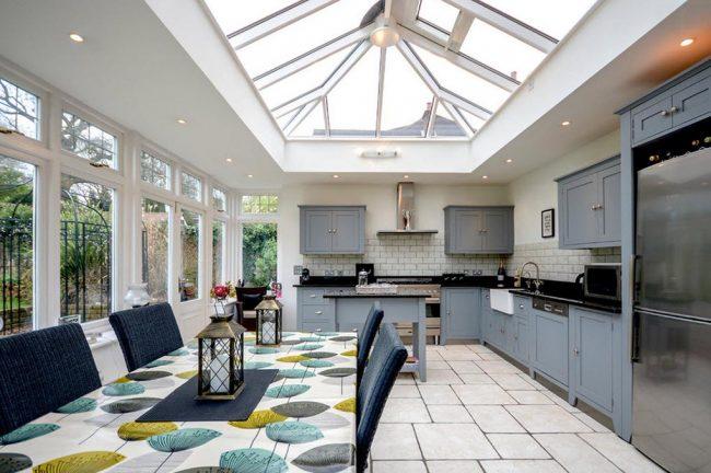 Большое количество естественного освещения в узкой панорамной кухне