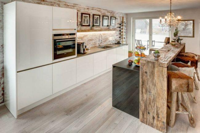 Барная стойка из дерева отлично вписывается в интерьер кухни-столовой свободной планировки