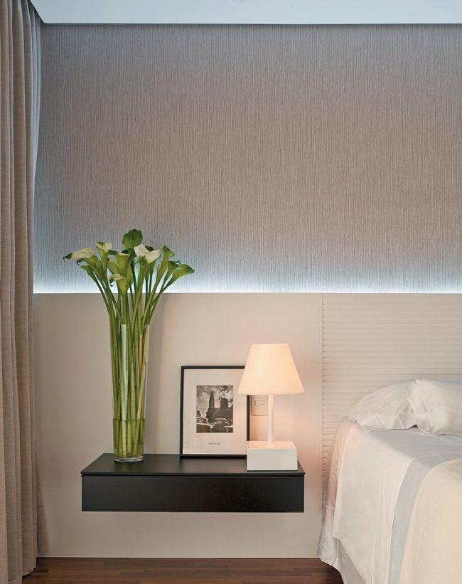 Обои под бетон в небольшой спальне, оформленные с помощью дополнительной подсветки