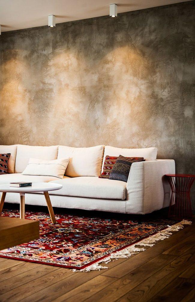 Очень реалистичные обои под бетон в гостиной. Теплая подсветка сверху, а также элементы скандинавского стиля придают комнате уютной атмосферы