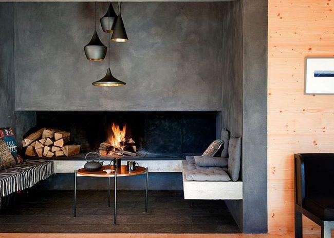 Небольшая каминная зона выделенная обоями под бетон, что отлично гармонируют с деревянными элементами интерьера