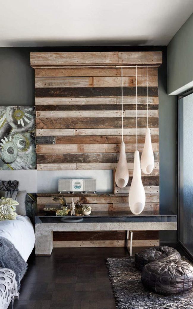 Обои под бетон в спальне, дополненные оригинальным дизайнерским решением оформления стены из натуральной древесины, а также фактурными элементами из различных тканей