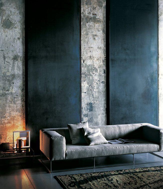 Большие холсты глубокого цвета индиго, которые отлично подчеркивают обои под бетон в интерьере гостиной комнаты