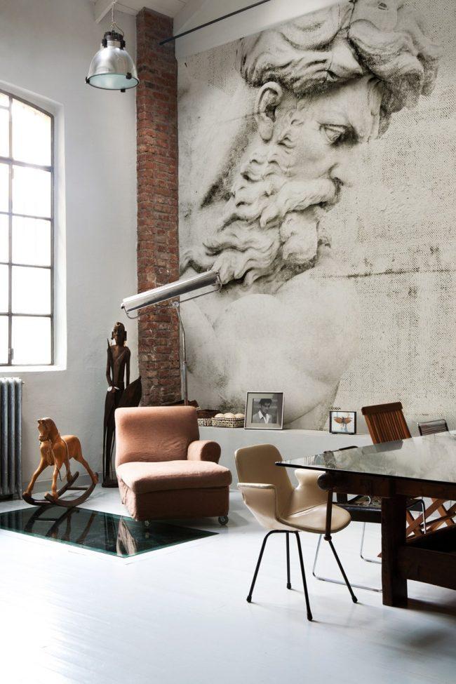 Гостиная с небольшой рабочей зоной в стиле лофт. На фото вы можете увидеть как гармонично сочетаются кирпичная кладка и обои под бетон с массивным рисунком