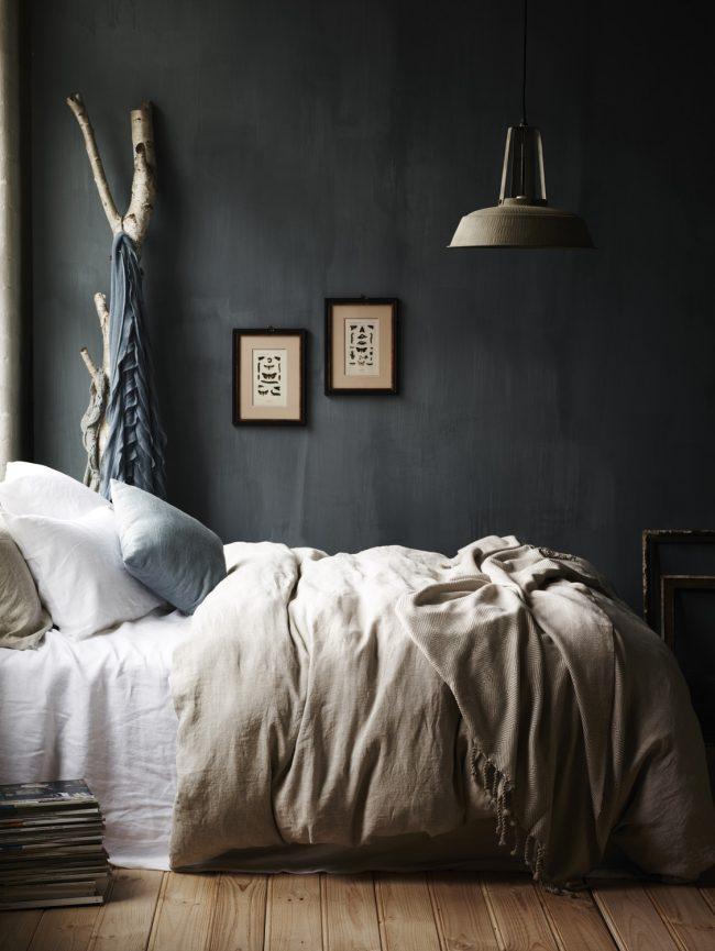 Темные обои под бетон придают спальной комнате уютной атмосферы