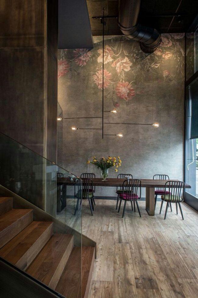 Лофтовая обеденная зона с обоями под бетон с нежным цветочным рисунком и деревянными элементами интерьера