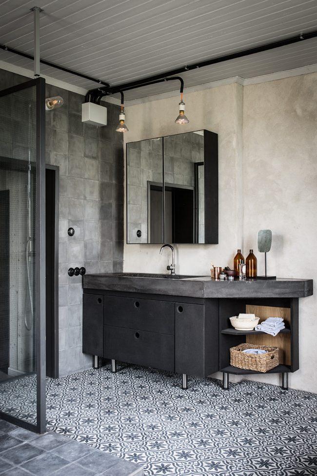 Светлые обои под бетон в небольшой ванной комнате отлично сочетаются с оригинальной орнаментальной плиткой