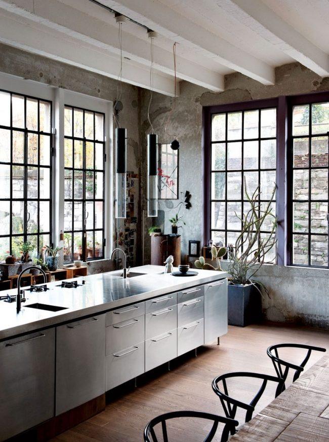 Просторная кухня с фактурными обоями под бетон, которые отлично сочетаются с металлической мебелью
