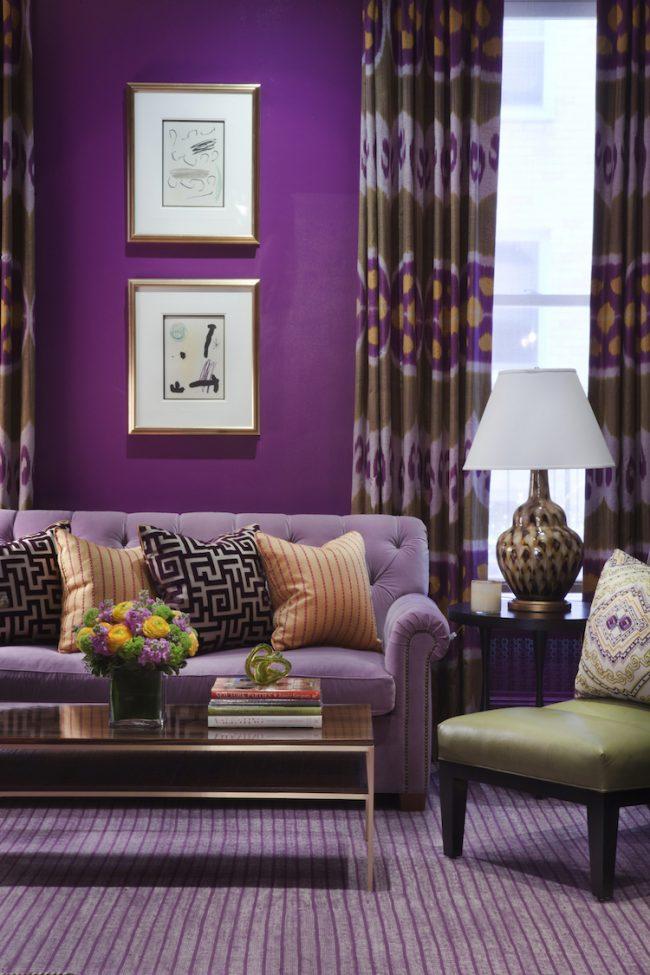 Насыщенные сиреневые обои в гостиной можно поддержать ковролином и, к примеру, большим диваном более светлых оттенков