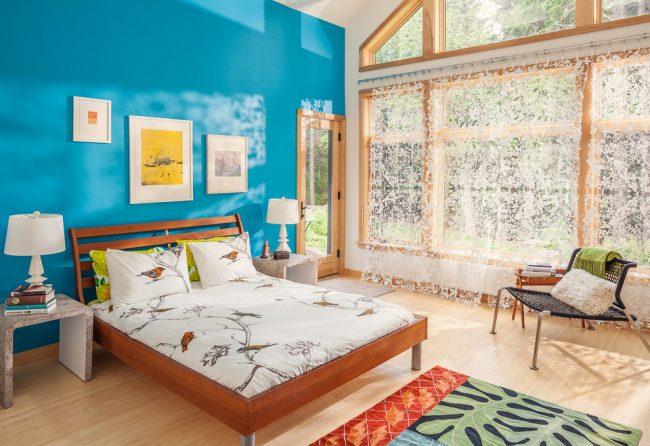 Небесно голубой окрас выделенной стены в спальной зоне