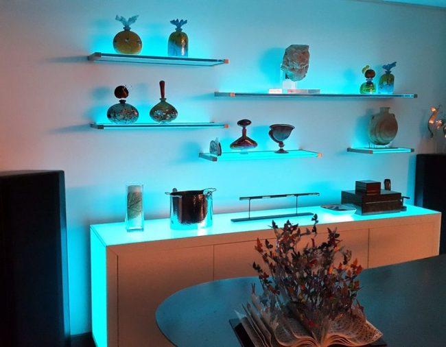 Синяя подсветка полок в гостиной способна выгодно изменить очертание предметов декора