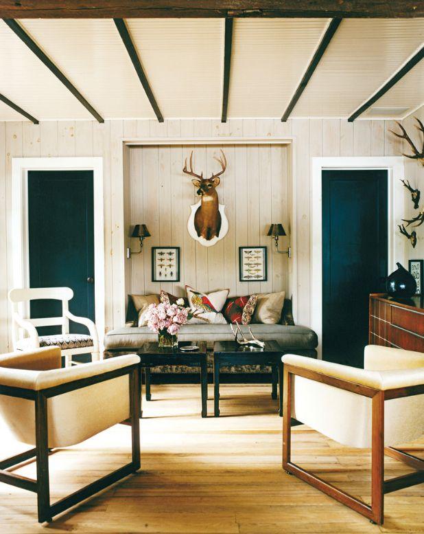 Интерьер в скандинавском стиле: темные двери, стульчики, журнальные столики и банки на потолке в сочетании со светлой обшивкой стен и текстилем
