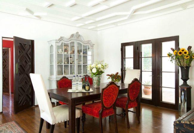 Классическая зона трапезы в загородном доме: темные фактурные дубовые двери двери, коричневый пол и светлый потолок с лепниной