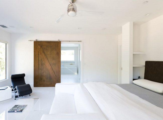 Темные двери из необработанной древесины в минималистическом белом интерьере
