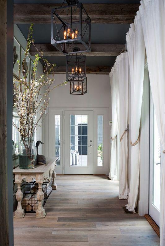 Кованные светильники в духе романтизма с лампами-свечами, высокие белые стены и темный потолок с деревянными балками напоминают загородный замок
