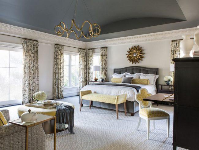 Классическая спальня в серых тонах: темный потолок, желтая обшивка мебели, серые шторы и белая мебель
