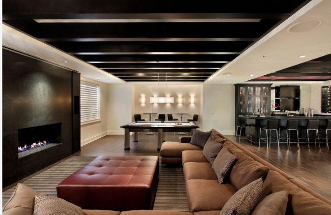 Деревянный потолок и пол дополнены мебелью в коричневых оттенках. Контраст создается за счет точечного освещения и белых стен