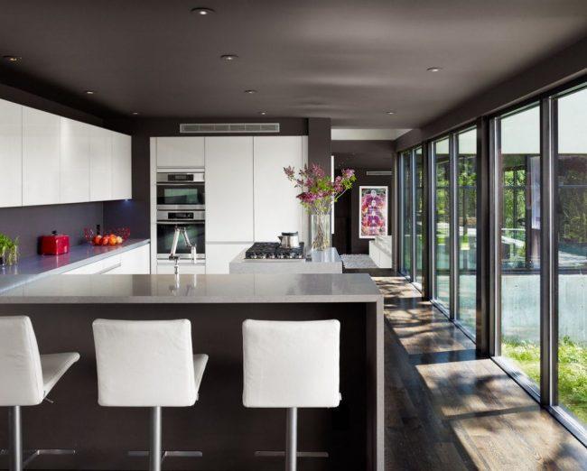 Темный потолок и панорамные окна на кухне загородного дома