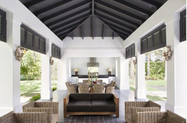 Темный потолок, светлые стены и большие окна в летнем домике для отдыха