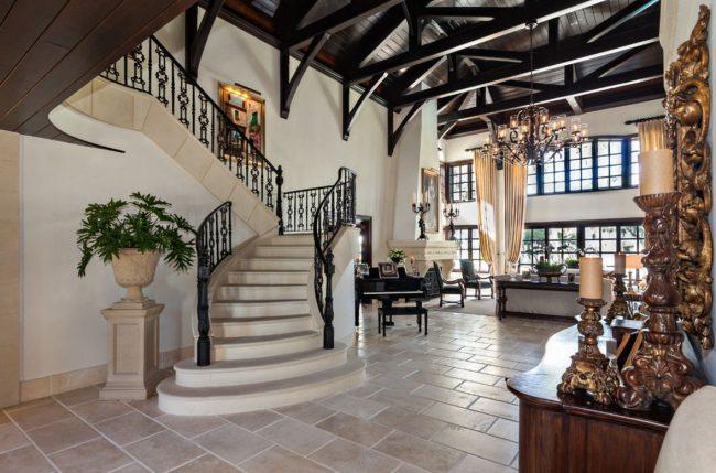 Классический интерьер загородного дома люкс-класса. Деревянный темный потолок, белые стены, мраморные ступени и резных элементов в декоре